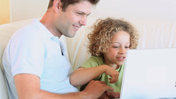 Father and son watching video on a laptop Stock Video Footage