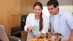 Couple cooking while reading the recipe on a lapto Stock Video Footage