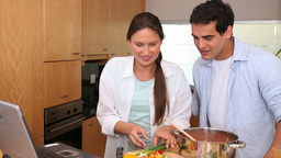 Couple cooking while reading the recipe on a lapto Footage