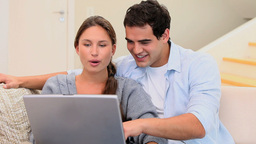Couple laughing while using laptop Footage