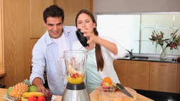 Couple putting fruits in a blender Footage