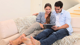 Couple using a tablet computer while sitting Stock Video Footage