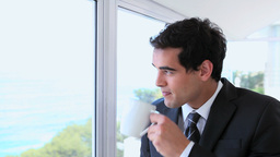 Businessman drinking coffee while looking outside Footage