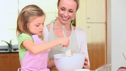 Girl cooking with her mother Stock Video Footage