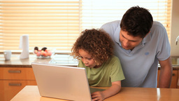 Boy using a laptop with his father Footage