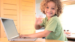 Boy typing on a laptop and waves at the camera Footage