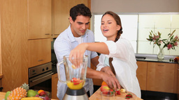 Couple putting fruits into a blender Footage