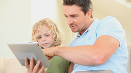 Father using an ebook with his son Stock Video Footage