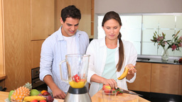 Woman putting a banana in a blender Stock Video Footage
