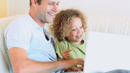 Boy laughing while watching video with his father Stock Video Footage