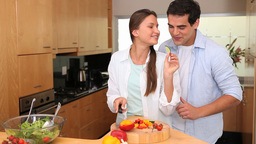 Man embracing his wife whos cutting vegetables Footage