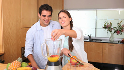 Woman adding fruits in a blender Footage