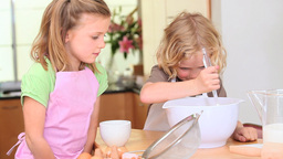 Little boy mixing a dough while his sister is helping Footage