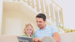 Man using a tablet while his son is watching Stock Video Footage