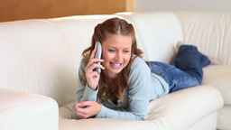 Young woman on the phone while lying Stock Video Footage