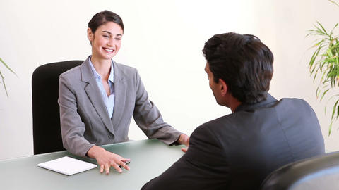 Business people talking while sitting at a desk Stock Video Footage