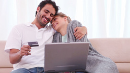 Couple using a credit card while sitting with a la Footage