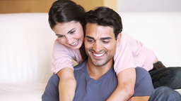 Smiling couple embracing while looking at a laptop Footage