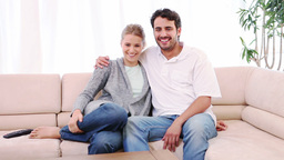 Couple sitting on a sofa while watching a movie Stock Video Footage