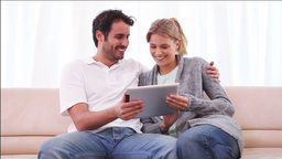 Smiling couple using a tablet computer Footage