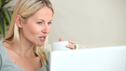 Woman looking at a laptop while drinking Footage