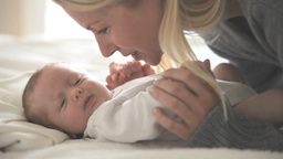 Woman kissing a baby who is lying on a bed Stock Video Footage