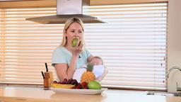 Mother eating an apple while holding her baby Footage