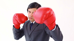 Serious businessman using boxing gloves Footage
