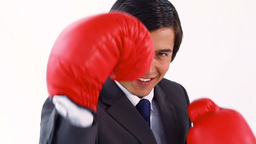 Smiling executive playing with boxing gloves Footage
