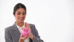 Businesswoman putting money in a piggybank Footage