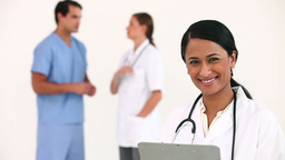 Female doctor posing in front of her colleagues Stock Video Footage