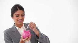 Woman dressed in a suit putting money in a piggyba Stock Video Footage