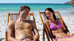 Smiling couple lying on deck chairs Footage