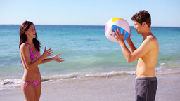 Happy couple playing with a beach ball Stock Video Footage