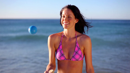 Smiling brunette playing with a ball Stock Video Footage