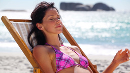 Brunette sitting on a deck chair Stock Video Footage