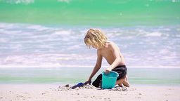 Blonde child playing with a shovel Live Action