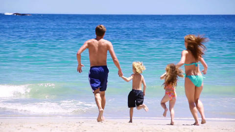 Smiling family running and splashing each other Stock Video Footage