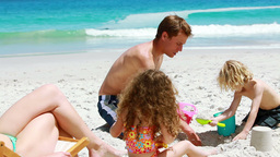 Father and his children building a sand castle Footage