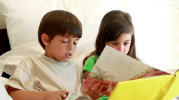 Siblings holding a book while reading it Footage