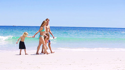 Smiling family walking on the sand Stock Video Footage