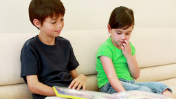 Children sitting while reading a book Stock Video Footage