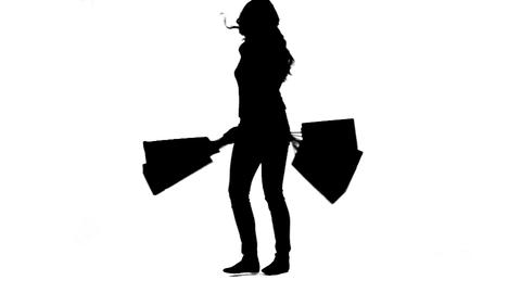 Silhouette of an energetic woman holding shopping  Footage