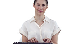 Businesswoman looking at camera while typing on a  Footage