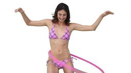 Woman in a bikini playing with a hula hoop Footage