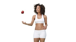 Woman in training clothes throwing an apple upward Footage