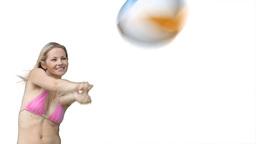Woman in a pink bikini playing beachball Footage