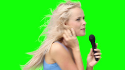 Blonde woman dancing while singing into a micropho Footage
