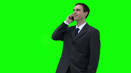 Businessman looking around while talking on a phon Footage