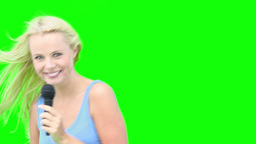 Blonde woman dancing while singing with a micropho Footage